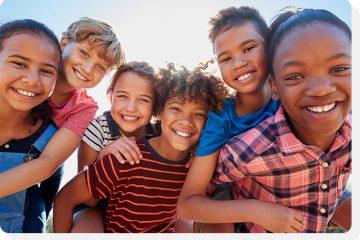 Crianças de várias idades reunidas e sorrindo